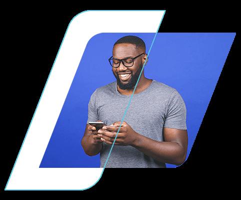 Homem sorrindo, segurando um celular e olhando para a tela