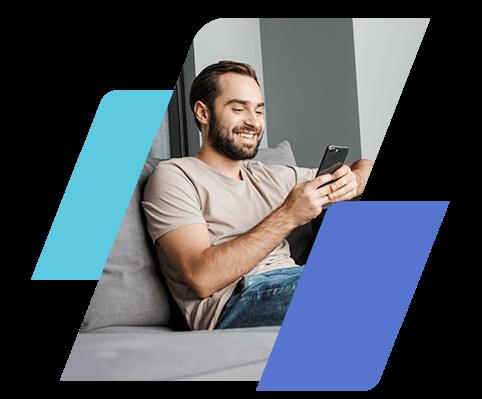 Homem sorrindo, sentado no sofá e segurando um celular